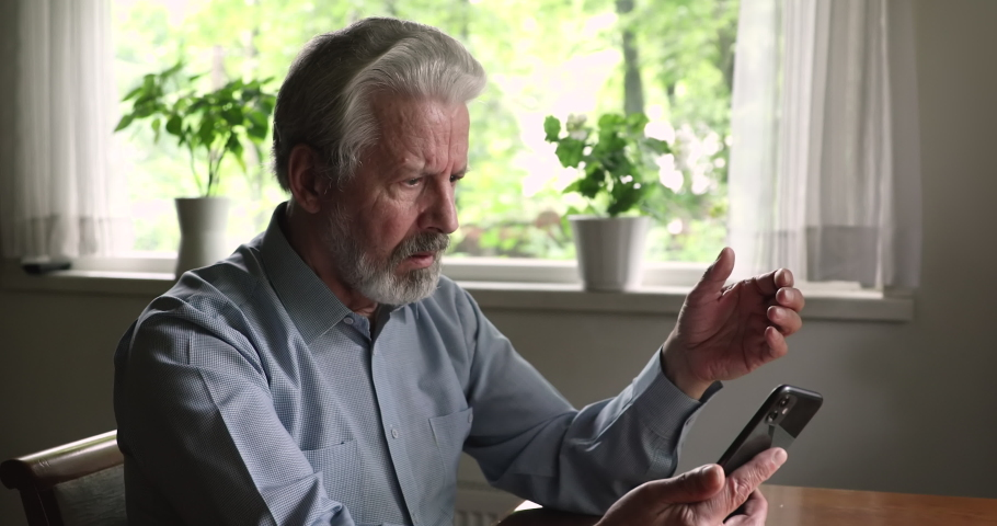 Serious angry grey haired old man sit indoor holding smart phone experiences difficulties with wireless modern gadget usage, wrong password, need device repair or help with app understanding concept Royalty-Free Stock Footage #1060968202