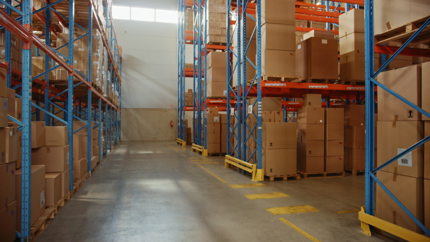 Gigantic Sunny Retail Warehouse full of Shelves with Goods in Cardboard Boxes. Logistics and Distribution Storehouse Center for further Product Delivery Packages. Descending Semi Side Camera View | Shutterstock HD Video #1060977025