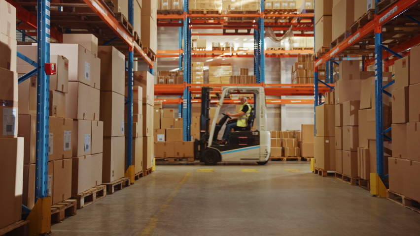 In Big Retail Warehouse Moving Sunlight Illuminates Shelves with Cardboard Boxes. Forklift Driving in Logistics, Distribution Center with Products Ready for Global Shipment, Customer Delivery | Shutterstock HD Video #1060977055