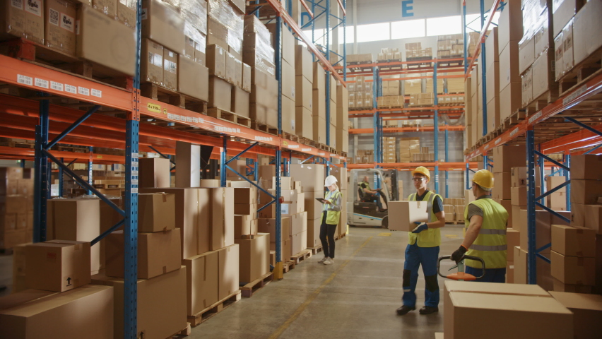 Retail Warehouse full of Shelves with Goods in Cardboard Boxes, Workers Scan and Sort Packages, Move Inventory with Pallet Trucks and Forklifts. Product Distribution Logistics Center. Descending Shot | Shutterstock HD Video #1060977073