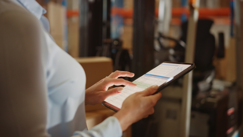 In Warehouse Manager Uses Digital Tablet with App to Check Package Delivery Status with Graphs, Infographics, and Statistics on Screen. Distribution Center with Shelves with Cardboard Boxes Royalty-Free Stock Footage #1060977106