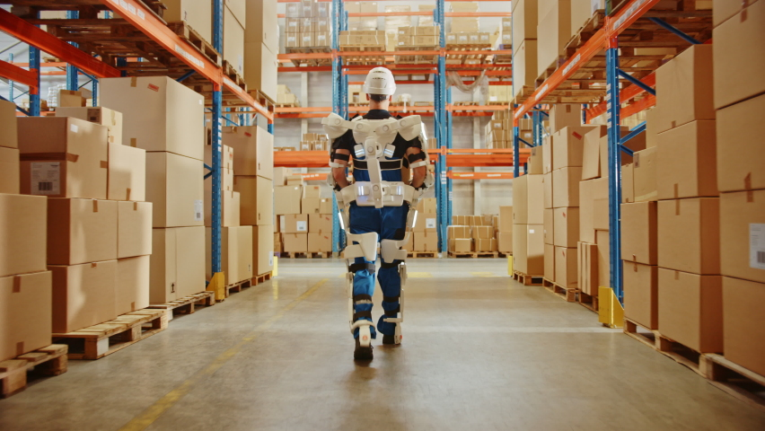 High-Tech Futuristic Warehouse: Worker Wearing Advanced Full Body Powered exoskeleton, Walks with Heavy Cardboard Box. Exosuit amplifies Human Performance, Strenght, Eliminates Work Related Injuries Royalty-Free Stock Footage #1060977157