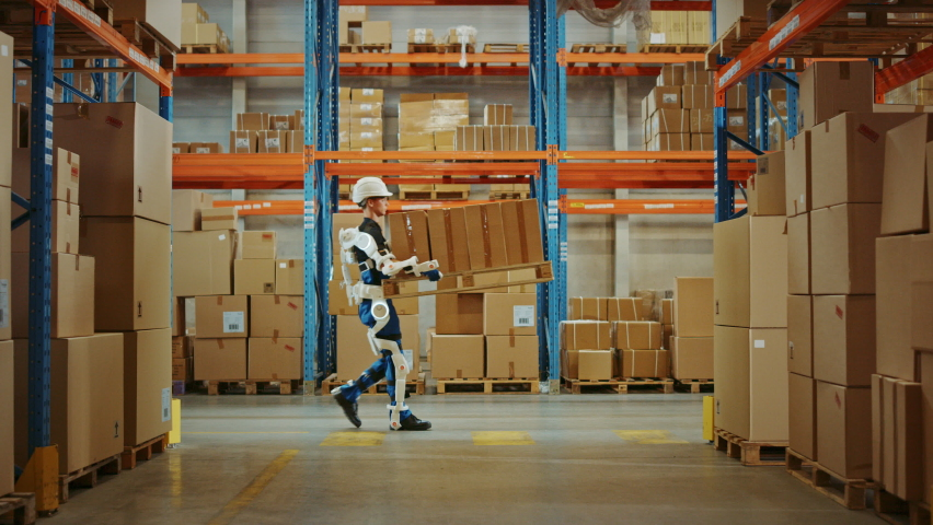 High-Tech Futuristic Warehouse: Manager Scans Packages for Inventory, Delivery in the Background Worker Wearing Advanced Full Body Powered exoskeleton, Walks with Heavy Pallet full of Cardboard Boxes | Shutterstock HD Video #1060977178