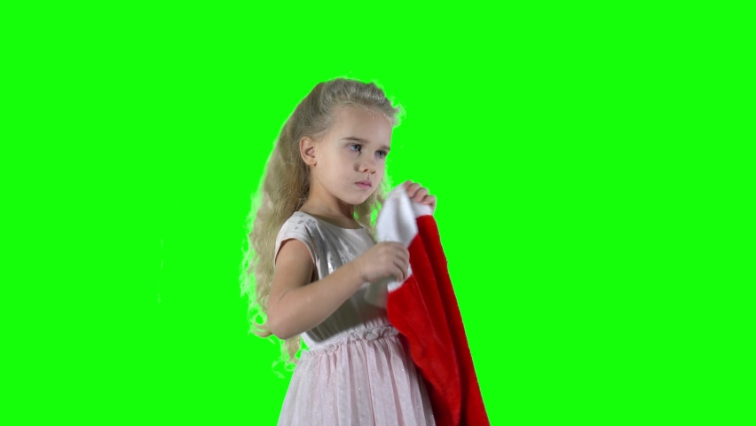 Awesome girl put on Christmas cap hat and smile looking at camera. Chroma key green screen background | Shutterstock HD Video #1060979647