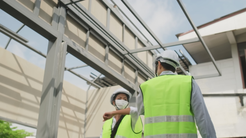 Asian workers people wearing protective face mask onsite of architecture due to covid pandemic crisis. Male and female engineers making elbow touch instead of handshake to avoid coronavirus infection. Royalty-Free Stock Footage #1060980193