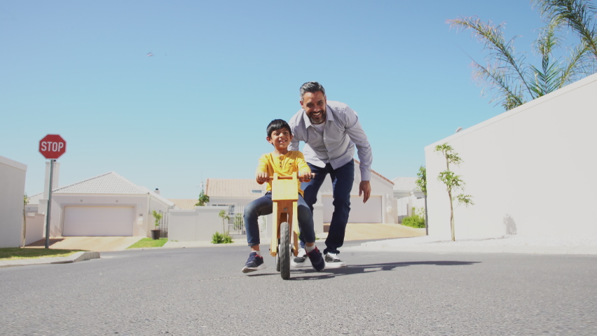 Happy latin father helping smiling boy to ride wooden balance cycle on street. Happy middle eastern child and young dad riding bike in lane. Smiling daddy teaching son to ride a balance bicycle.