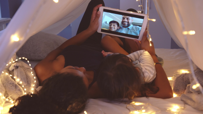 Mother and cute girl using digital tablet while lying in kid tent doing a video call with father and son. Indian family in online conversation with each other during quarantine and social distancing.