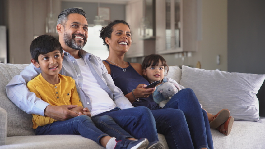 Happy indian man and african woman relaxing with daughter and son watching television at home together. Cheerful ethnic family relaxing on sofa at home watching movie with children. Royalty-Free Stock Footage #1060982713