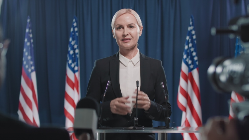 Portrait of Caucasian woman running for USA presidency starting election debates in front of journalists, medium shot