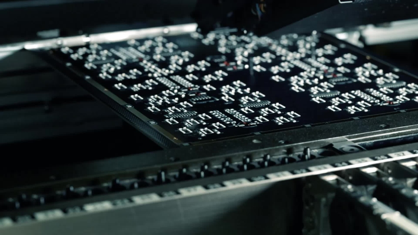 Electronic Printed Circuit Board Being Assembled with Automated Robotic Arm. Surface Mounted Technology Connecting Microchips, Transistors, Capacitors to the Motherboard in a factory. Macro Close-up. Royalty-Free Stock Footage #1060984834