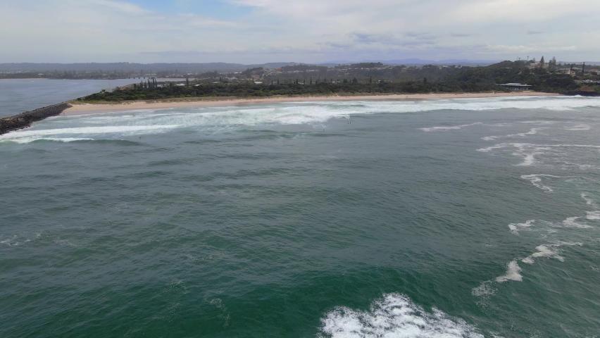 Rippling Blue Sea With Waves Crashing On The Sea Wall - Sharpes Beach In Skennars Head - NSW, Australia - aerial drone