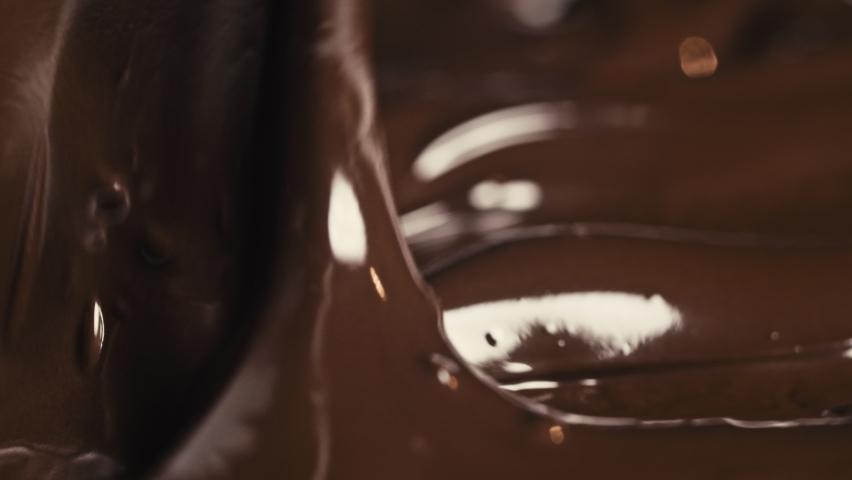 Chocolate. Pouring melted liquid premium dark chocolate. Close up of molten liquid hot chocolate swirl. Confectionery. Confectioner prepares dessert. slow motion. | Shutterstock HD Video #1060987351