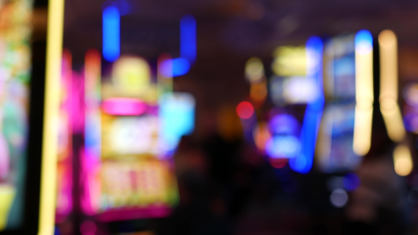 Defocused slot machines glow in casino on fabulous Las Vegas Strip, USA. Blurred gambling jackpot slots in hotel near Fremont street. Illuminated neon fruit machine for risk money playing and betting. | Shutterstock HD Video #1060987354