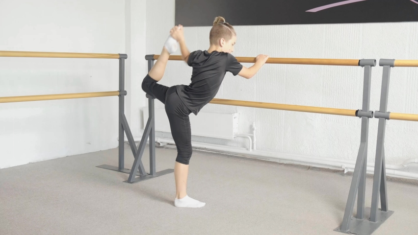 Young blond boy stretches his leg up. Flexible slim body. Warm-up before playing sports. | Shutterstock HD Video #1060987840