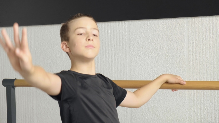 The boy is dancing ballet, one hand on the barre, the other to the side. Dance training at a ballet school, for children, boys and girls. | Shutterstock HD Video #1060987876