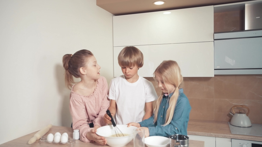 Cute children prepare dough for pizza, pie and cookies in the kitchen. Mix the dough with a whisk. Beautiful bright kitchen. | Shutterstock HD Video #1060987885