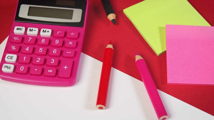 White paper and calculator and crayons on a red desk. High quality 4k footage | Shutterstock HD Video #1060988587
