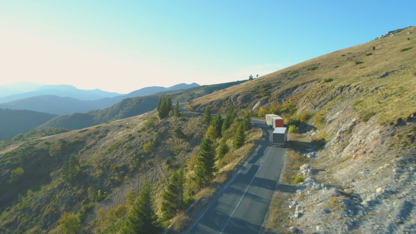 Aerial View Of Trucks with trailers driving on curvy mountain road in the summer Royalty-Free Stock Footage #1060988704