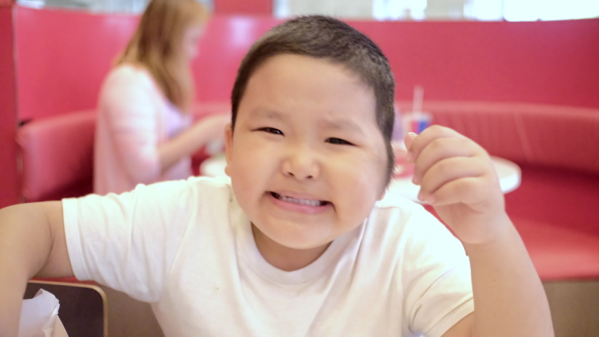Happy little asian boy eating fried chicken chop in the restaurant.