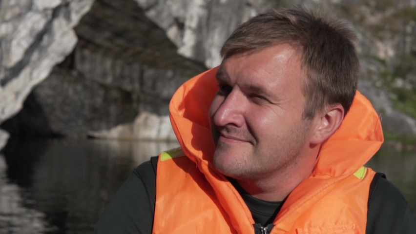 A happy man in a life jacket swims on a boat on a mountain lake. | Shutterstock HD Video #1060990147