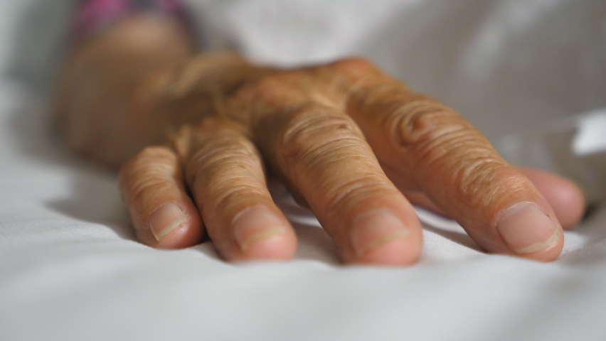 Granddaughter takes and gently touches wrinkled arm of sick mature grandma lying in bed hospital. Girl comforts hand of her old grandmother in medical clinic. Daughter gives support to her mother | Shutterstock HD Video #1060992136