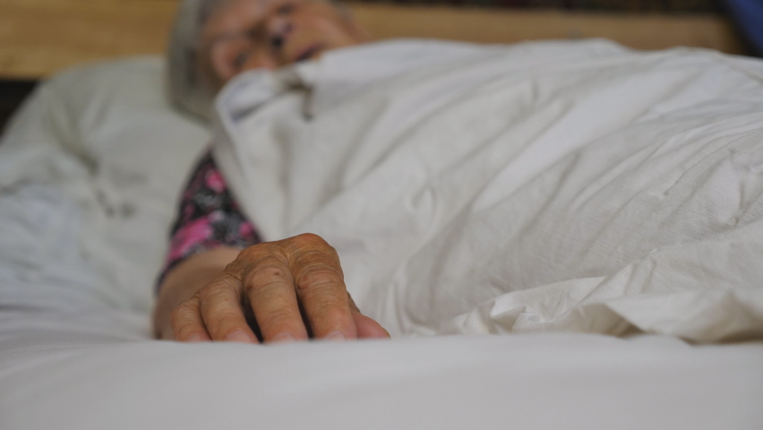 Granddaughter takes and gently touches hand of her elderly grandmother in medical clinic. Girl comforts wrinkled arm of sick mature woman lying in bed hospital. Concept of care and love. Slow motion | Shutterstock HD Video #1060992139