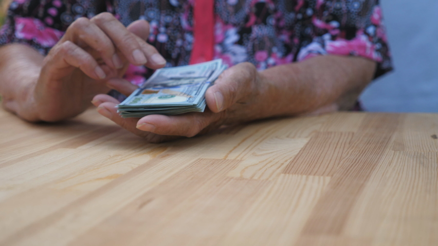 Dolly shot hands of elderly grandmother holds bundle of money and scatters foreign currency on the desk. Arms of old granny throws one hundred dollar bills on the table in front to camera. Slow motion | Shutterstock HD Video #1060992142