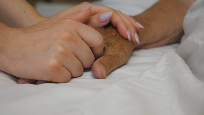 Granddaughter holds and comforts hand of her grandmother in medical clinic. Daughter gently touches wrinkled arm of sick mature mother lying in bed hospital. Concept of care and love. Slow motion | Shutterstock HD Video #1060992145