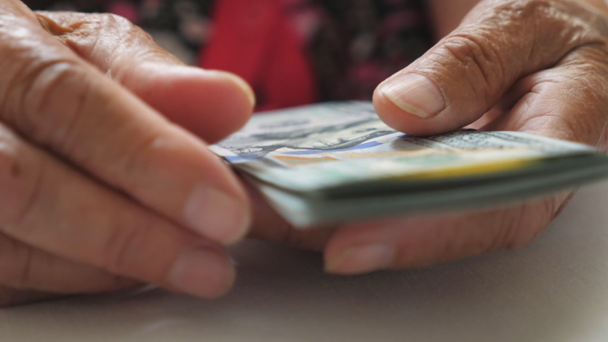 Elderly woman holds cash in arms and counts foreign currency over the table. Close up hands of old grandmother puts one hundred dollar banknotes on the desk. Money concept. Low view Slow motion | Shutterstock HD Video #1060992157