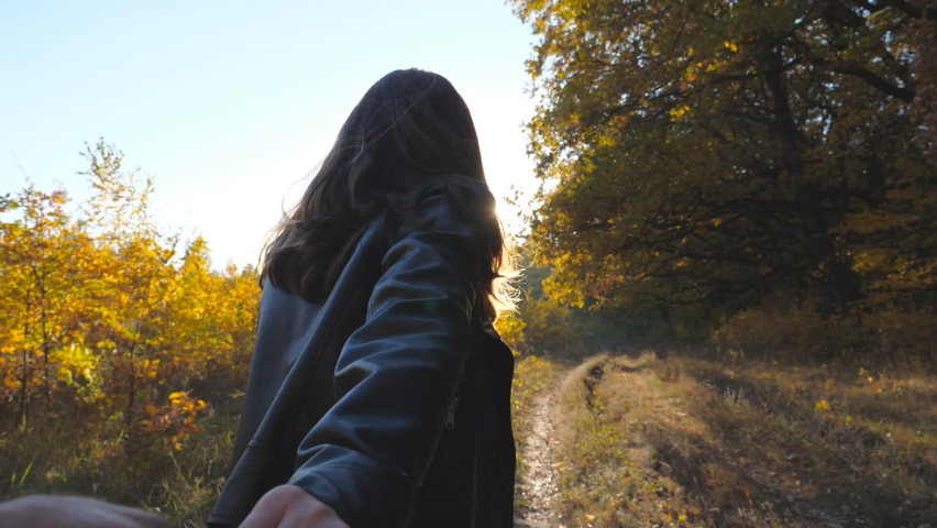 Follow me shot of happy girl leads her boyfriend along trail near autumn forest. Young woman holds male hand and runs along path near woodland. Beautiful nature at background. Concept of loving. POV | Shutterstock HD Video #1060992166