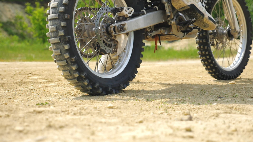 Close up wheel of powerful off-road motorcycle starting movement and kicking up dry ground or dust. Motocross bike starts movement. Concept of motorsport or active lifestyle. Slow motion Back view | Shutterstock HD Video #1060992172