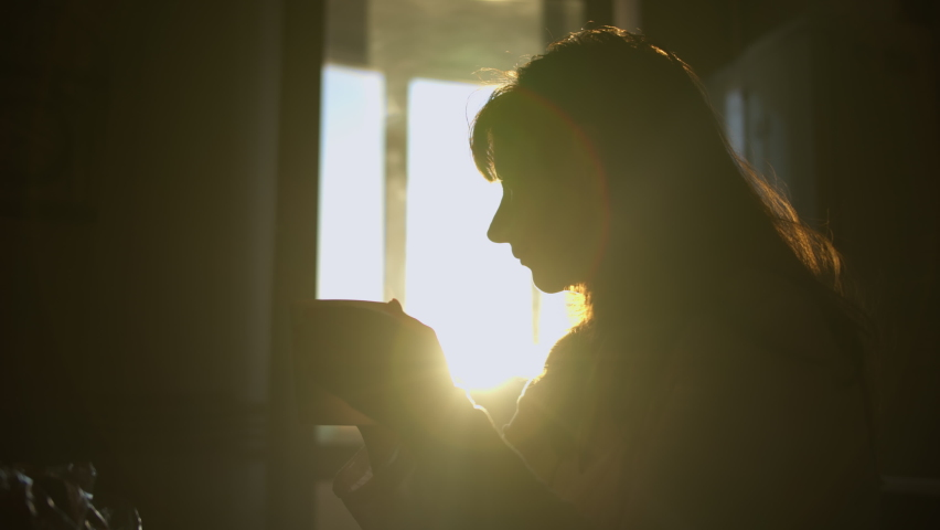 Silhouette of a woman drinking coffee early in the morning at home, alone, sun rays | Shutterstock HD Video #1060996882