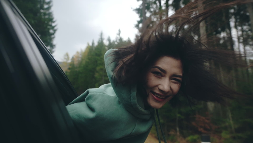Close-up of asian girl traveler with long black hair traveling, sitting in front seat of car, crawling out of window and enjoying wind. Woman riding car and laughing, her face cuting by wind.