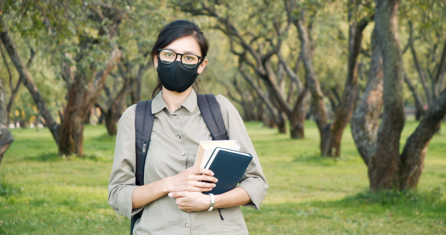 Portrait of a young woman wearing a protective mask holding a book and looking at the camera outdoors. Concept of education during a pandemic. | Shutterstock HD Video #1061000656