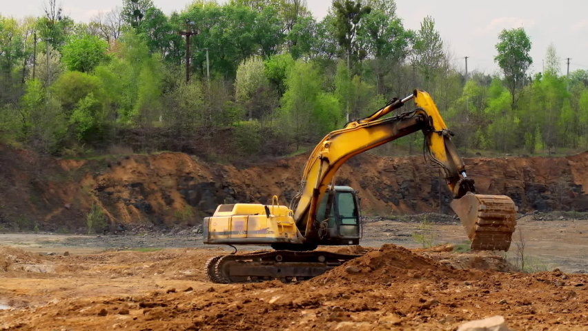 Earth moving equipment. Yellow excavator digging the ground. Excavator bucket scoops up the soil on nature background. Slow motion.