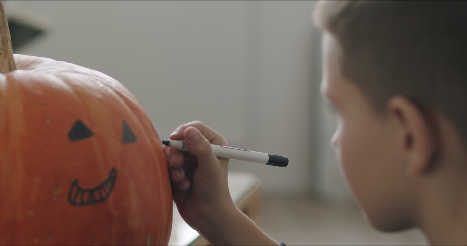 Close-up of kid drawing halloween holiday decoration on punpkin . Social campaign for pandemic coronavirus covid-19 prevention. | Shutterstock HD Video #1061004988