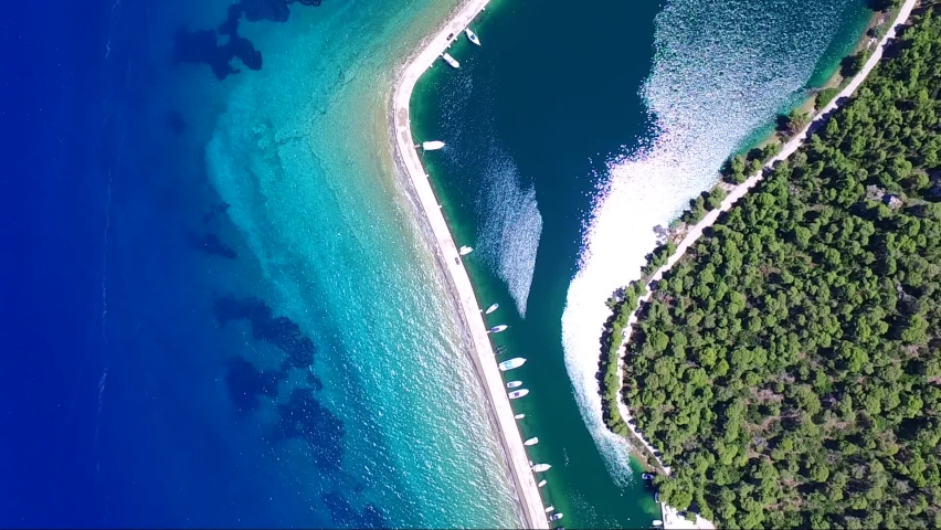 Overhead aerial shot from drone of Mavrolimni bay and fishing port, Greece, with beautiful glimmering and shining sea with tones of blue and turquoise | Shutterstock HD Video #1061008213