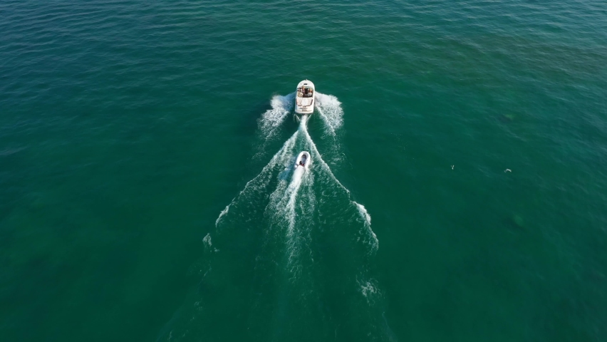 A large boat with a motor pulls a white inflatable boat on a trailer. Top view of boats in motion on shallow water | Shutterstock HD Video #1061009491