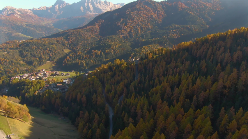 AERIAL: Flying towards a small town surrounded by the autumn colored Dolomites. Picturesque aerial shot of a vast valley in the Italian Alps changing colors on a sunny day in October. Leaf peeping | Shutterstock HD Video #1061012821