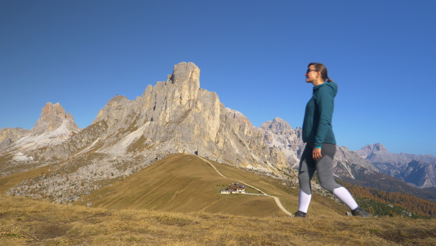 SLOW MOTION: Fit Caucasian woman goes hiking in the picturesque Dolomites. Young female traveler hikes along a path overlooking Passo Giau, a stunning mountain pass in Italian Alps on sunny fall day. | Shutterstock HD Video #1061013190