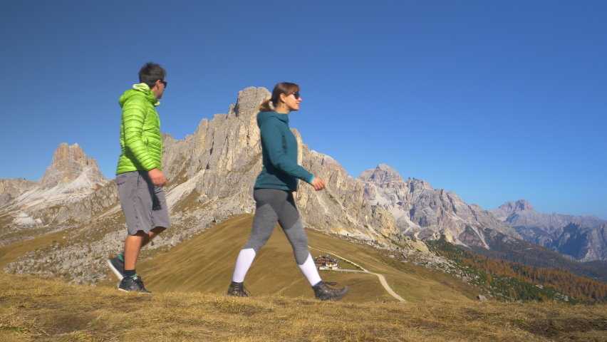 SLOW MOTION: Fit Caucasian couple hikes along a trail overlooking Passo Giau. Young Caucasian woman leads the way for her boyfriend as they goes hiking in the Dolomites on a sunny fall afternoon. | Shutterstock HD Video #1061013457