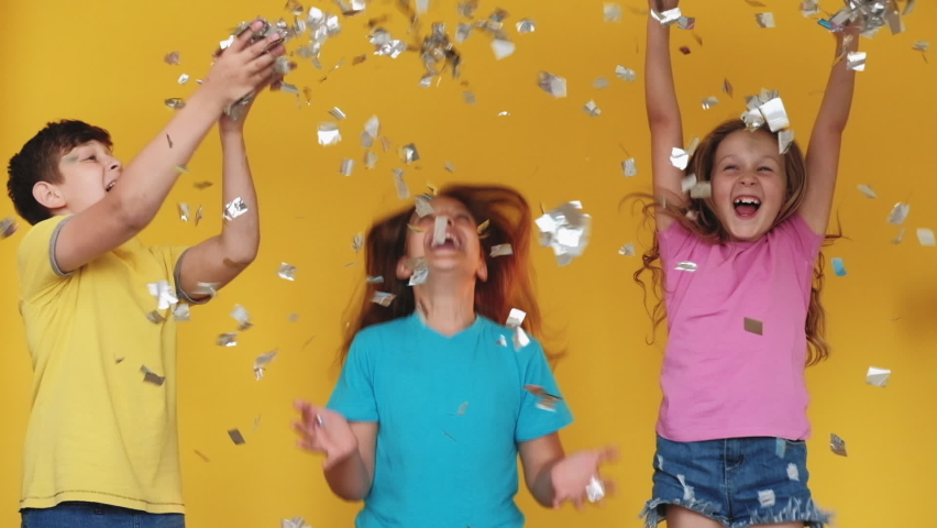 Kids party. Holiday joy. Fun celebration. Amused excited children enjoying entertainment dancing in confetti rain isolated on yellow background. Royalty-Free Stock Footage #1061014699