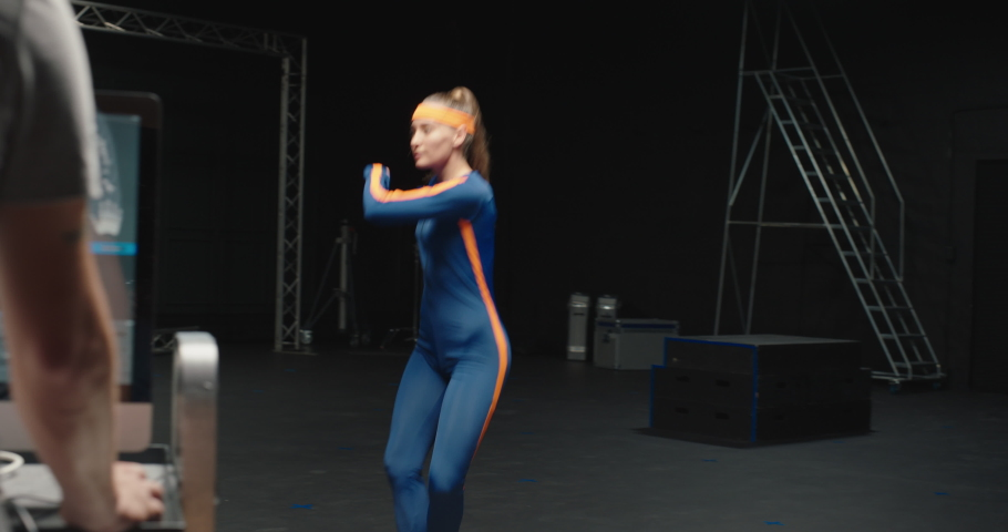 Woman wearing motion capture suit dancing in studio ballet dancer girl wearing mo-cap suit for 3d character animation for virtual reality technology | Shutterstock HD Video #1061018557
