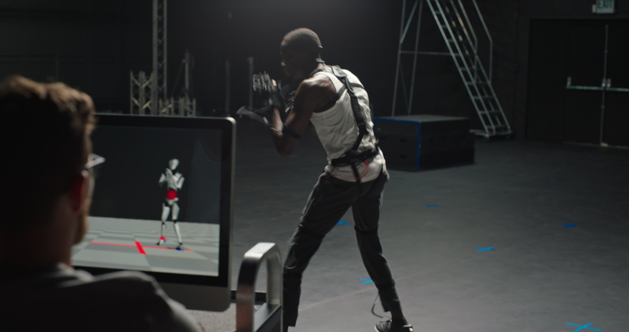 Fit man wearing motion capture suit in studio fighting computer gaming martial arts actor boxing wearing mo-cap suit for 3d character animation for virtual reality fighting game | Shutterstock HD Video #1061018566