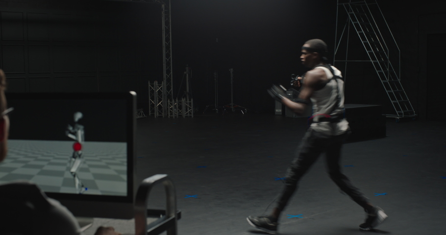 Fit man wearing motion capture suit in studio fighting computer gaming martial arts actor boxing wearing mo-cap suit for 3d character animation for virtual reality fighting game | Shutterstock HD Video #1061018575