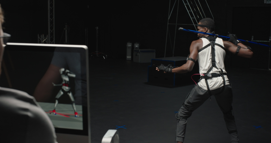 Mocap man wearing motion capture suit in studio performing bo staff sword fighting martial arts actor wearing mo-cap suit for 3d character animation for virtual reality gaming industry | Shutterstock HD Video #1061018581
