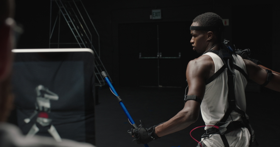 Mocap man wearing motion capture suit in studio using escrima sticks fighting martial arts actor wearing mo-cap suit for 3d character animation for virtual reality gaming industry | Shutterstock HD Video #1061018584