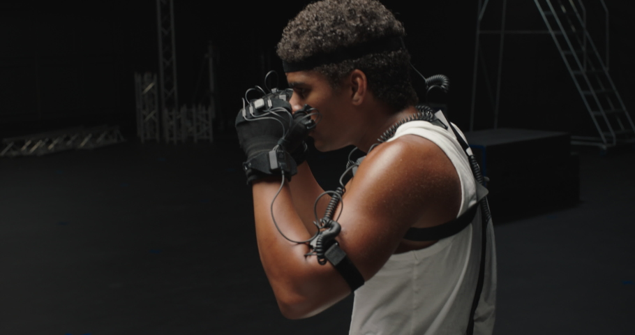 Man wearing motion capture suit in studio performing martial arts actor boxing wearing mo-cap suit for 3d character computer game animation for virtual reality fighting gaming | Shutterstock HD Video #1061018587