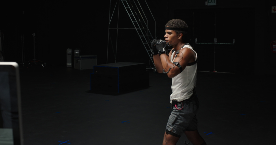 Man wearing motion capture suit in studio performing martial arts actor boxing wearing mo-cap suit for 3d character computer game animation for virtual reality fighting gaming | Shutterstock HD Video #1061018590