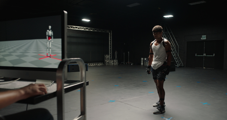 Man wearing motion capture suit in studio performing martial arts actor boxing wearing mo-cap suit for 3d character computer game animation for virtual reality fighting gaming | Shutterstock HD Video #1061018599